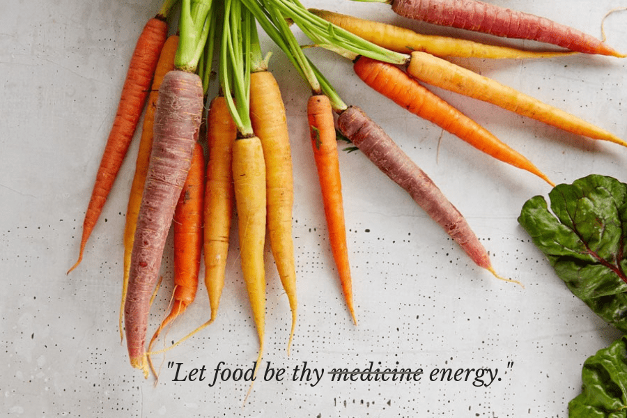 """A photo of a handful of carrots with the text """"Let food be thy medicine/energy"""""""