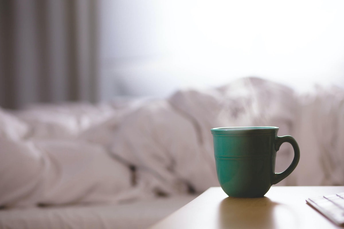 A warm drink on a night table next to a bed