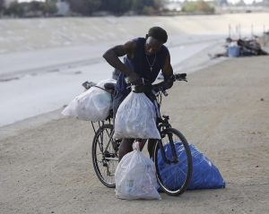 Man carrying plastic bags on his bicycle